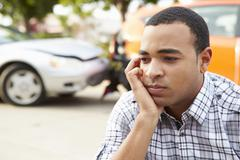 Worried Male Driver Sitting By Car After Traffic Accident - stock photo