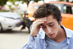 Worried Teenage Driver Sitting By Car After Traffic Accident - stock photo