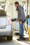 Male Driver Filling Car At Gas Station - stock photo
