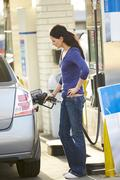 Female Driver Filling Car At Gas Station - stock photo