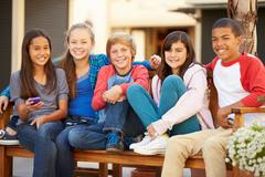 Group Of Children Sitting On Bench In Mall Stock Photos