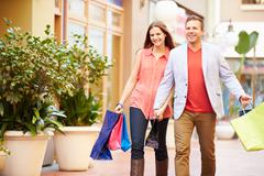 Young Couple Walking Through Mall With Shopping Bags Stock Photos