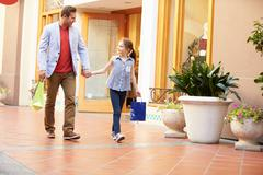 Father And Daughter Walking Through Mall With Shopping Bags Stock Photos