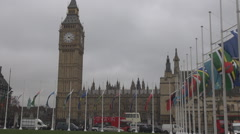 Wesminster square, national flags waving, cars move in London, crowded traffic Stock Footage