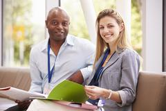 Portrait Of Two College Tutors Having Discussion Together Stock Photos