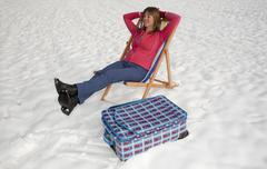 Winter time in the UK Holiday maker with deckchair and suitcase in a snow cov Stock Photos