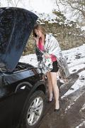 Woman driver telephoning for assistance at the roadside during winter conditi Stock Photos