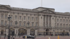Small british cars driving in front of Buckingham Palace building, cloudy day Stock Footage