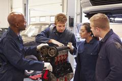 Teacher Helping Students Training To Be Car Mechanics - stock photo