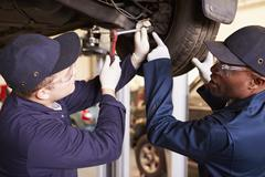 Teacher Helping Student Training To Be Car Mechanics - stock photo