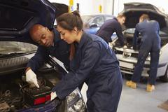 Teacher Helping Student Training To Be Car Mechanics Stock Photos