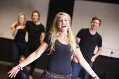 Students Taking Singing Class At Drama College Stock Photos
