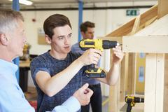 Teacher Helping College Student Studying Carpentry - stock photo