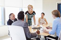 Five Businesspeople Having Meeting In Boardroom Stock Photos