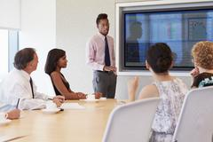 Businessman By Screen Addressing Boardroom Meeting - stock photo