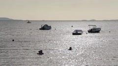 Boats moored on beautiful silvery gray sea swimmers silhouette 1 Stock Footage