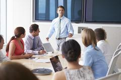 Motivational Speaker Talking To Businesspeople In Boardroom - stock photo