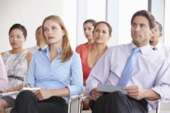 Business Delegates Listening To Presentation At Conference - stock photo