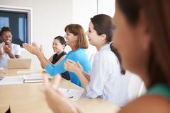 Businesspeople Applauding Colleague In Boardroom Stock Photos