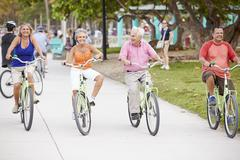 Group Of Senior Friends Having Fun On Bicycle Ride Stock Photos