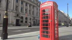 Red phone booth in London, english call box landmark, car traffic, sunny day Stock Footage