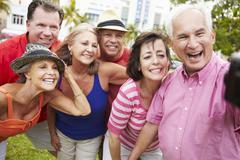 Group Of Senior Friends Taking Selfie In Park - stock photo