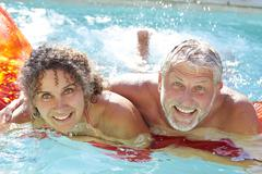 Mature Couple Relaxing On Airbed In Swimming Pool - stock photo