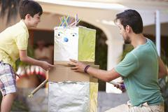 Father And Son Building Model Robot In Garden - stock photo