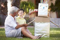Grandfather And Grandson Building Model Robot In Garden - stock photo