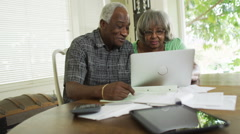 Happy senior African couple paying off bills on laptop - stock footage