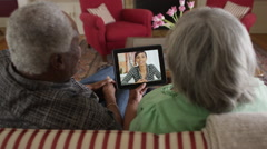 Senior African couple video chatting with tablet Stock Footage