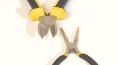 Needle-nose pliers and mini cutters on white, rotation, close up Stock Footage