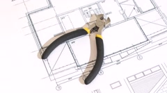 Wire cutters with yellow, gray handle on building plan, scheme, rotation Stock Footage