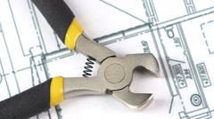 Wire cutters with yellow, gray handle on building plan, scheme, rotation, close Stock Footage