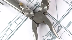 Metal round-nose pliers on building plan, scheme, rotation, close up Stock Footage