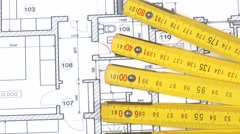 Part of yellow folding rule on building plan, rotation Stock Footage