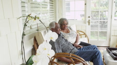 Senior African couple sitting on couch talking - stock footage