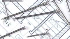 Metal nails on building plan, close up, rotation Stock Footage