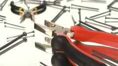 Gray and red pliers and gray, yellow round-nose pliers on white among nails - stock footage