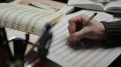 Musician writes notes in the music book - stock footage