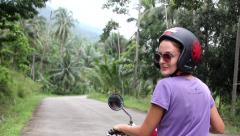 Young Woman In Hemlet Rides Scooter on a Beautiful Jungle Road Stock Footage