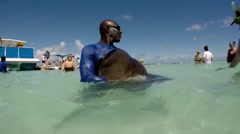 Antigua Caribbean Sea 240 man holds a stingray in his arms Stock Footage
