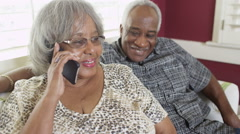Happy senior black couple talking on smartphone at home Stock Footage