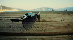Sunglasses lying on the beach and reflect the silhouettes of people passing Stock Footage