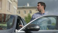 Young man coming out of the black car Stock Footage