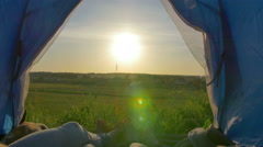 The pair sit, lie in the camping tent by sky background Stock Footage