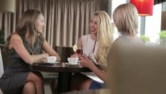 Three beautiful women met in a cafe - stock footage