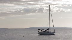 Sailing Yacht Boat moored, silvery gray sky, sea, horizon, islands, clouds 2 Stock Footage