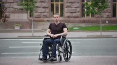 Invalid man sit in the wheel chair in the crowd stream at sidewalk - stock footage