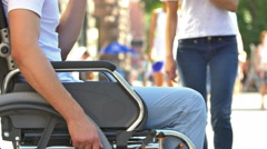 The invalid man sit in the wheel chair and take money from the going by people - stock footage